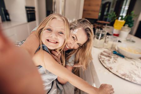 Happy family taking a selfie in kitchen