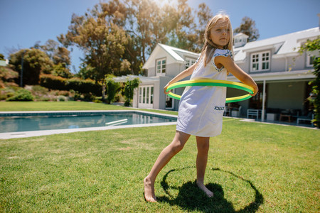 Cute little girl playing with hula hoop in the backyard