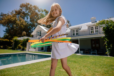 Smiling girl playing with hula hoop outdoors