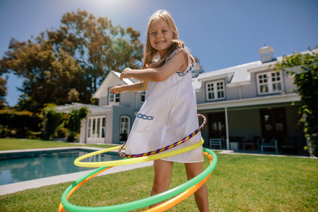 Little girl rotating hula hoop outdoors in her backyard
