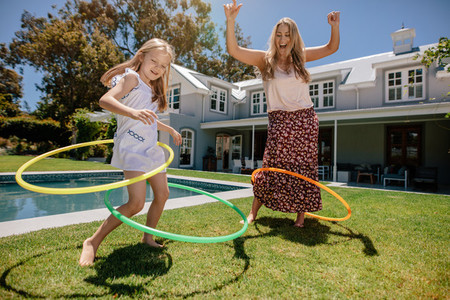Mother and daughter playing with hula hoop in their backyard