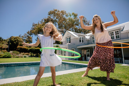 Happy mother and daughter twirling hula hoops