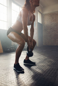 Muscular young woman exercising with kettlebell