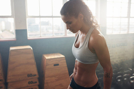 Fitness female taking a break from intense workout at the gym