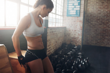 Fit woman taking a break from her workout at a gym