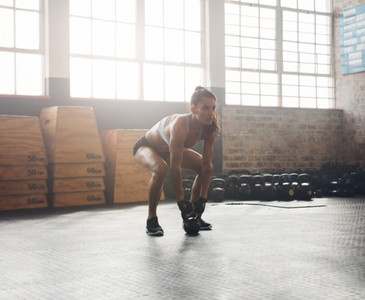 Muscular woman doing crossfit workout at gym