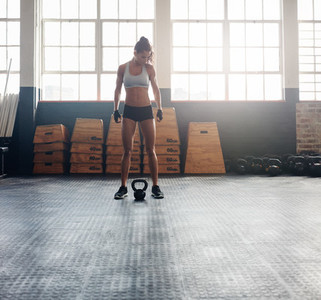 Tough fitness woman with kettle bell on floor