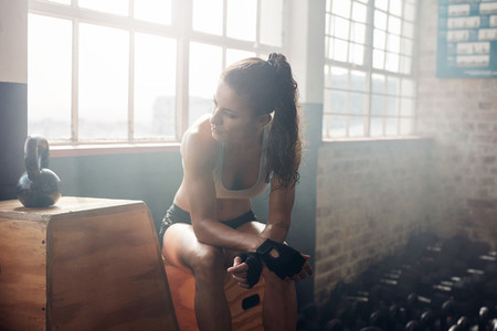Female athlete taking rest after exercising at gym