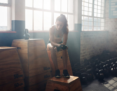 Female athlete taking break after exercising at gym