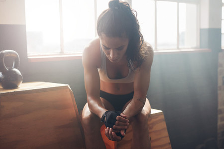 Female athlete taking rest after fitness training at gym