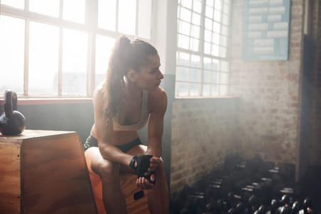 Female athlete woman having a rest after exercise at gym