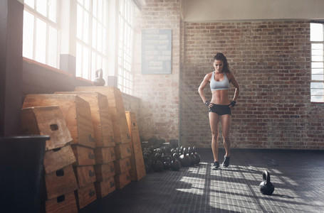 Fit young woman walking in the crossfit gym