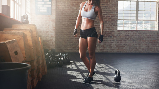 Muscular woman standing in crossfit gym