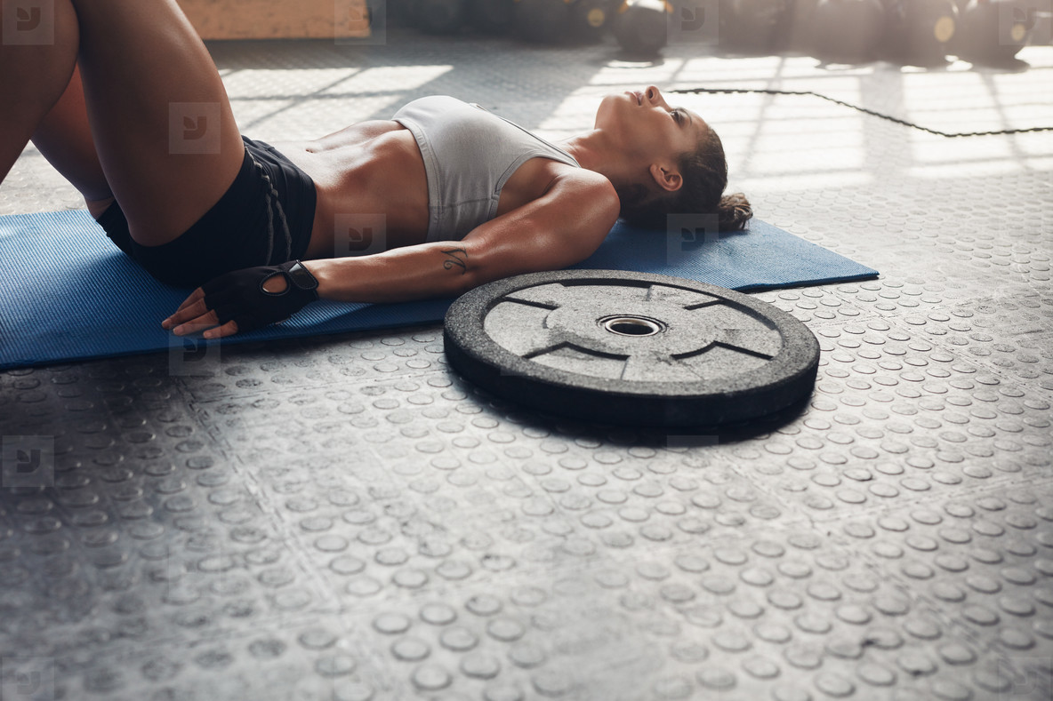 Muscular female relaxing after heavy weight workout