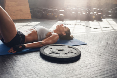 Fitness woman relaxing after heavy weight workout