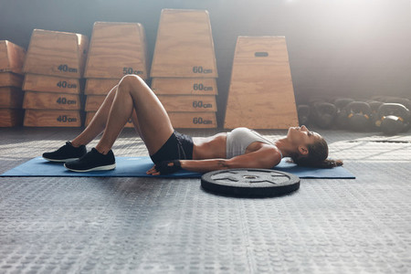 Fitness woman lying on her back after a gym workout