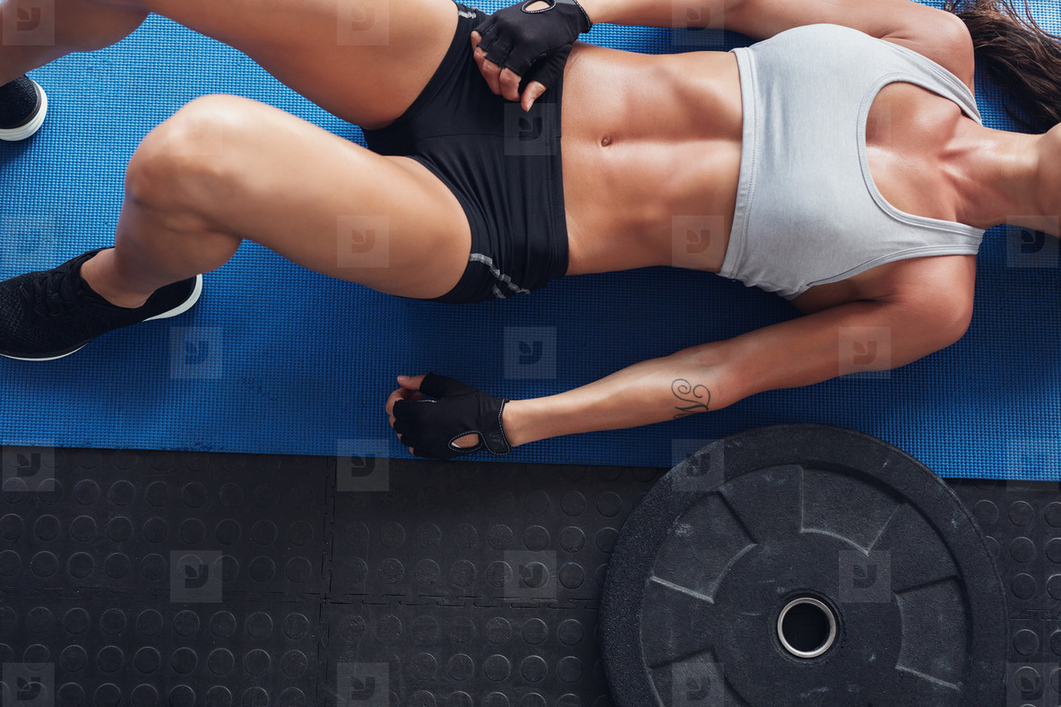 Muscular female on exercise mat with weight plate