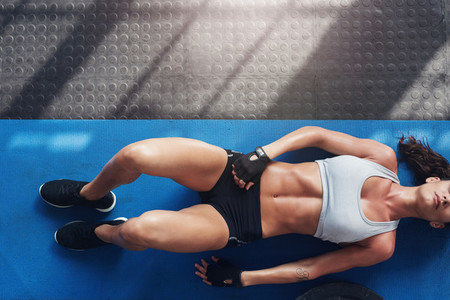 Muscular young woman lying on exercise mat