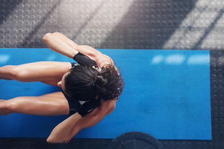Muscular young woman doing sit ups on an exercise mat