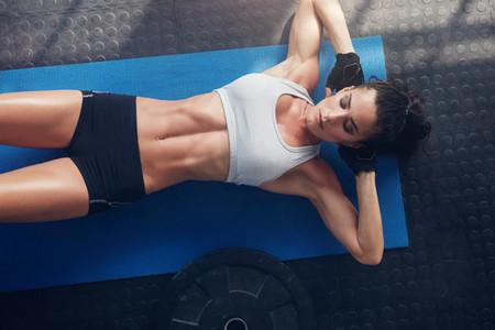 Fitness woman exercising on yoga mat