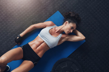 Muscular young female athlete relaxing after workout