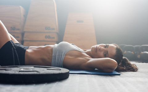Muscular female relaxing after exercise session