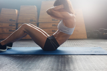 Muscular young woman doing stomach exercises