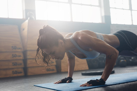 Young woman doing push ups at the gym