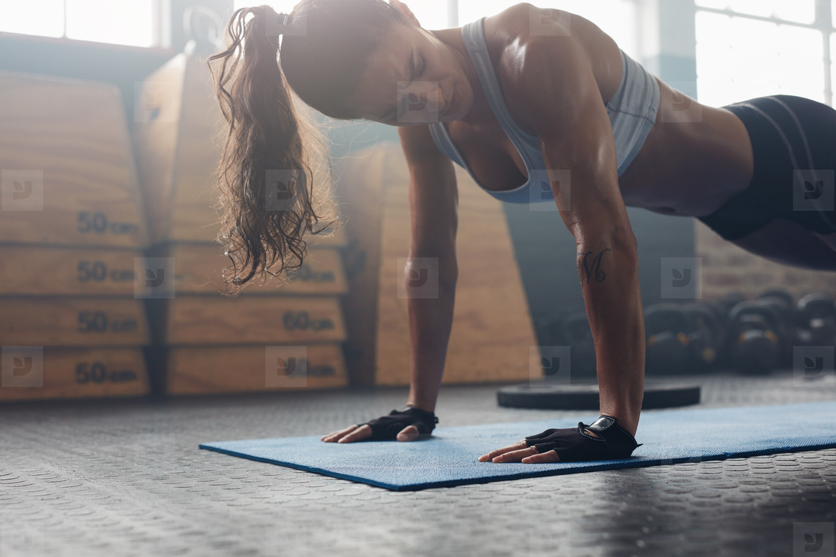 Strong young woman doing push ups in gym