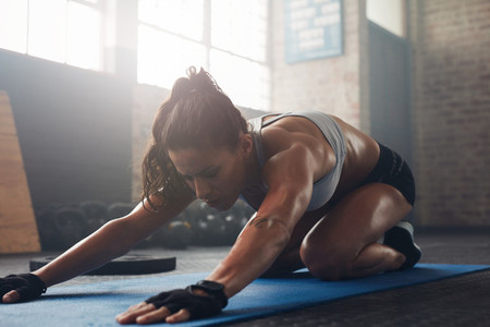 Young woman doing yoga on the gym floor