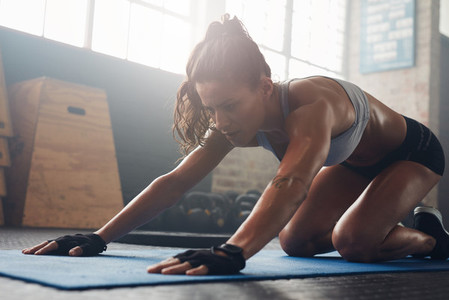 Young muscular woman doing stretching workout