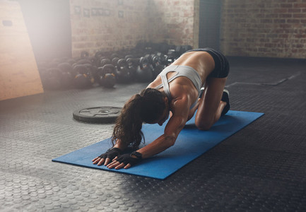 Young woman doing exercise on fitness mat