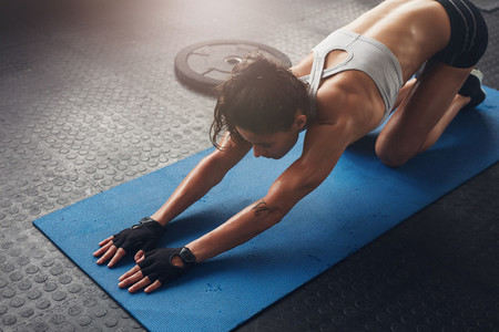 Woman on fitness mat doing stretching workout at gym