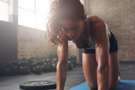 Muscular woman exercising at fitness club