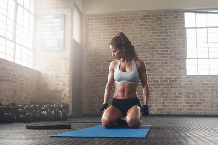 Fitness young woman sitting on yoga mat at gym