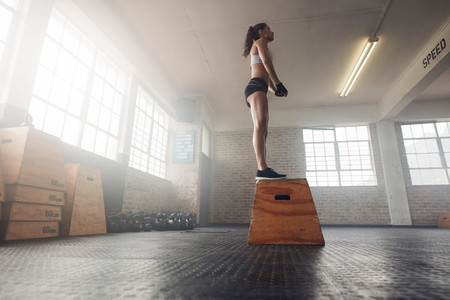 Fit young female standing on a box at gym