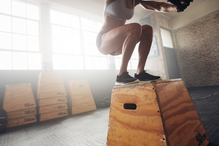 Fit young woman box jumping at a crossfit gym