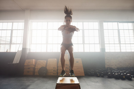 Young woman working out with a box at the gym