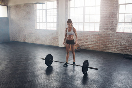 Strong crossfit female at gym with barbells