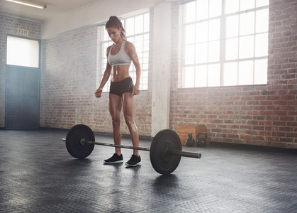 Fitness young woman at gym with barbell