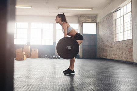 Fitness woman doing weight lifting at health club