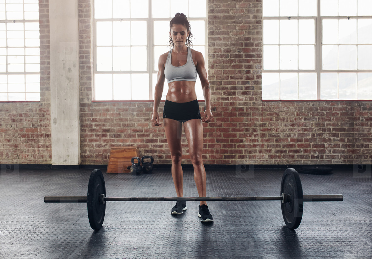 Fit young woman standing at gym with barbells on floor