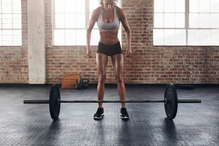 Muscular young woman exercising with heavy weights