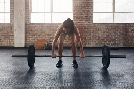 Fit young woman working out with a barbell