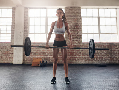Tough young woman exercising with barbell