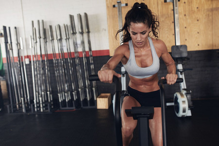 Fit young female working out on gym bike