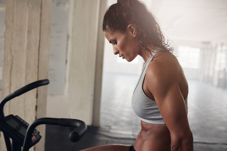 Muscular woman exercising on gym bike