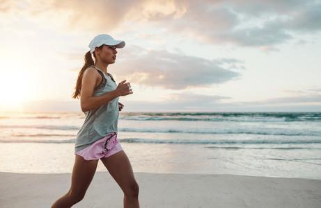 Beautiful young woman jogging on beach