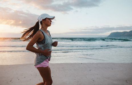 Fit young woman jogging at the beach in morning