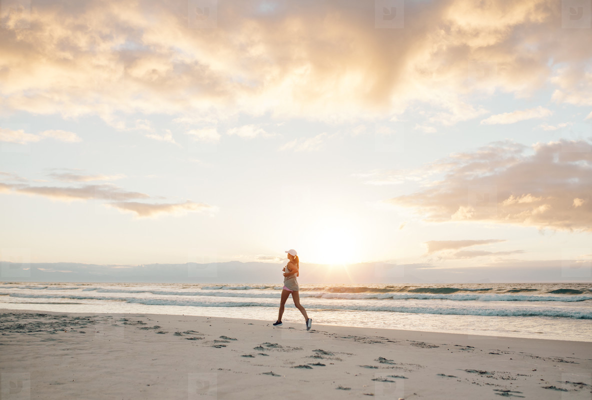 Healthy female jogging on the sea shore